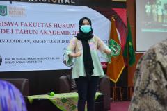 Dirigen sedang memandu lagu Indonesia raya dalam kegiatan yudisium fakultas hukum di Aula Blok I Lantai IV Unas.