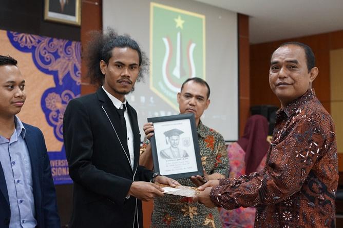 Dekan Fakultas Ilmu Sosial dan Ilmu Politik Dr. Zulkarnain, S.I.P., M.Si. (kanan) memberikan cinderamata kepada mahasiswa terbaik prodi Ilmu Politik Yintrosius Bena (kiri)