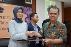 Wakil Dekan Fakultas Ilmu Sosial dan Ilmu Politik Bidang Akademik Dr. Ahmad Muksin, M.Si. (kanan) memberikan cinderamata kepada mahasiswa terbaik prodi Hubungan Internasional Sabrina Odelia Damara (kiri)