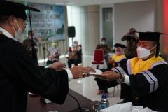 Penyerahan Sertifikat dan Souvenir oleh Wakil Direktur Sekolah Pascasarjana Universitas Nasional kepada Lulusan Terbaik Magister Hukum, Frans Katha Palayukan dalam Yudisium Magister Hukum Sekolah Pascasarjana Universitas Nasional pada hari Sabtu, 19 Juni 2021