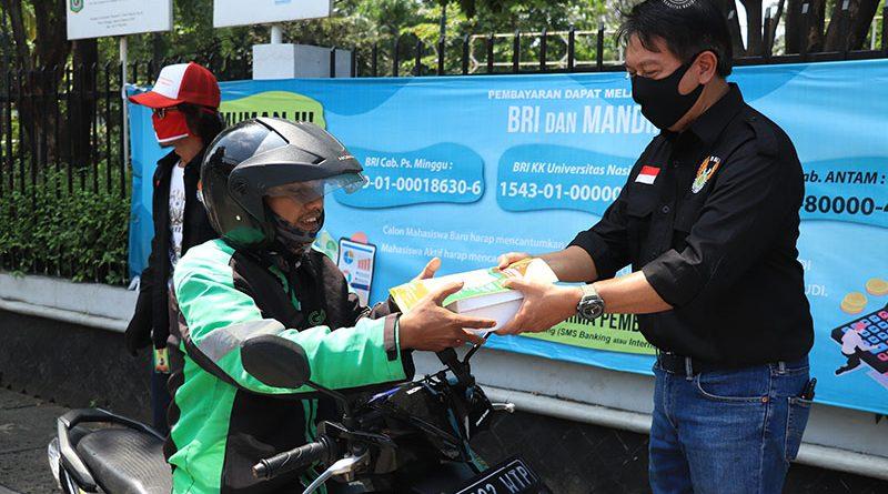 Ketua Umum UNBC yang juga Kepala Biro Administrasi Umum Universitas Nasional Drs. Ian Zulfikar, M.Si. memberikan bantuan makanan kepada driver online di kampus Unas Pejaten, Rabu 22 April 2020